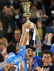 Napoli&#39;s captain Paolo Cannavaro holds the trophy after the final of the Cup of Italy at the Olympic Stadium in Rome. Napoli defeated Juventus 2-0