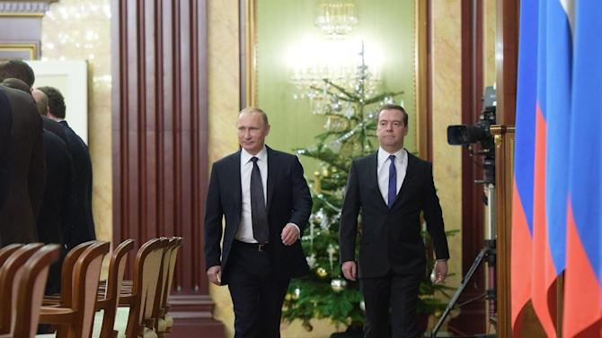 """Russian President Vladimir Putin, left, and Prime Minister Dmitry Medvedev walk to hold a cabinet meeting in Moscow, Russia, Thursday, Dec. 25, 2014.  Russian President Vladimir Putin has scrapped New Year's holidays for government ministers because of the unfolding economic crisis. Putin told a televised government session on Thursday that Cabinet ministers """"cannot afford"""" to go on holiday. (AP Photo/RIA Novosti, Alexei Nikolsky, Presidential Press Service)"""