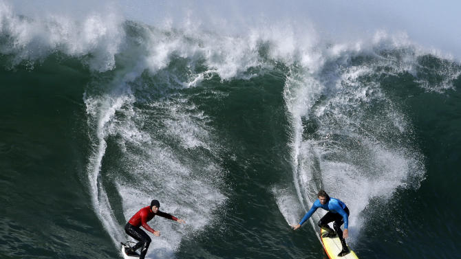 Tyler Smith, left, and Ryan Seelbach ride a wave together during heat 3 of the Mavericks Invitational big wave surf contest in Half Moon Bay, Calif., Sunday, Jan. 20, 2013. (AP Photo/Marcio Jose Sanchez)