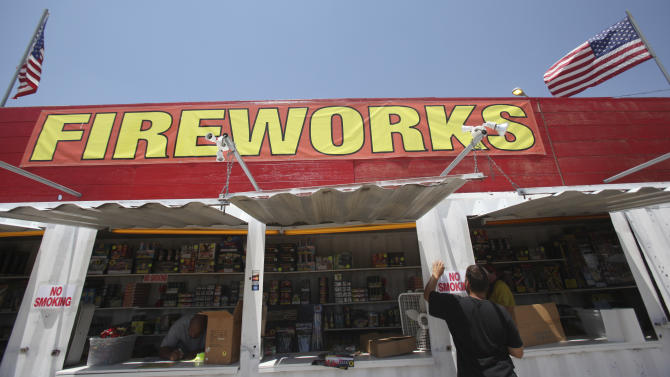 In this June 30, 2011 photo, Josh Wessner tapes up a no smoking sign at a fireworks stand in Lincoln Park, Texas. From Texas to Arizona to Georgia, there will be fewer oohs and aahs at the rockets' red glare this Fourth of July: Many cities and counties across the drought-stricken region are banning fireworks because of the risk of wildfires. (AP Photo/LM Otero)