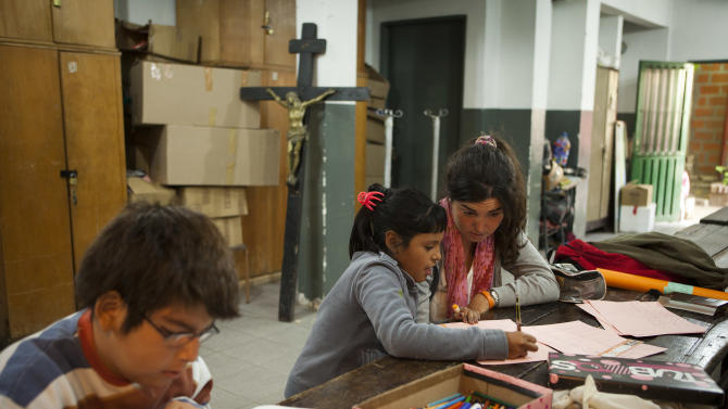 Volunteer Constanza Lascumbres, top right, teaches reading to Nicole Farias, 9, at the Virgin of Caacupe church in a shantytown in Buenos Aires, Argentina,  Thursday, March 14, 2013. At Villa 21-24, a slum so dangerous that most outsiders wouldn't dare go in, Jorge Mario Bergoglio often showed up unannounced over the course of more than 20 years. For many at the slum's Caacupe Virgin of the Miracles Church, it's nothing short of a miracle that the same man is now the pope. (AP Photo/Victor R. Caivano)
