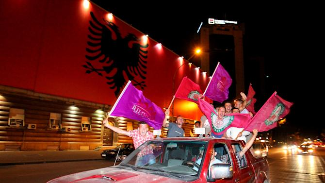 Supporters of the opposition Socialists celebrate in Albania's capital Tirana after counting results show a clear lead of their party, Tuesday, June 25, 2013 after Albania's national elections, seen as key test for the country's hopes for closer ties with the European Union. (AP Photo/Hektor Pustina)