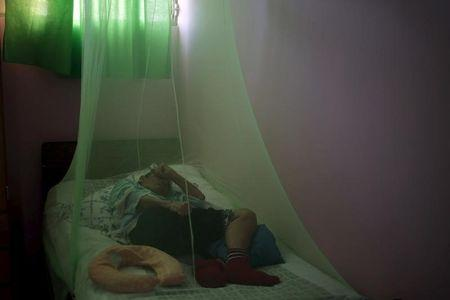 A man lies under a mosquito net in a home for the elderly in Masaya City