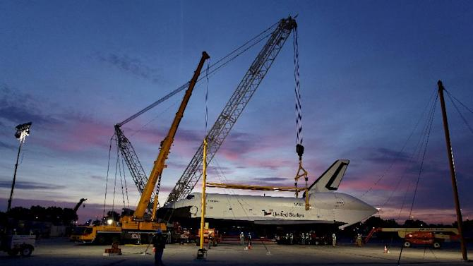 The sun rises as the space shuttle Enterprise rests on a specialized transporter after it was lifted from a NASA 747 Shuttle Carrier Aircraft at John F. Kennedy International Airport in New York, Sunday, May 13, 2012, in preparation for its upcoming journey to its new home at the Intrepid Sea, Air & Space Museum. Enterprise has been separated from the NASA 747 Shuttle Carrier at John F. Kennedy International Airport, just weeks after flying over New York City. Next month it will be taken by barge to the aircraft carrier USS Intrepid, the floating air-and-space museum that will be the shuttle's permanent home. The shuttle is scheduled to open to the public in mid-July. (AP Photo/Craig Ruttle)