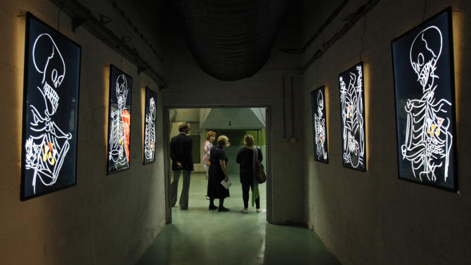 Visitors take a tour of contemporary art with light painting on walls left and right by artist Edo Murtic from Croatia, displayed at the war bunker, near town of Konjic, 80 kms south of Sarajevo, Bosnia, on Friday, April 26, 2013, as the once secret bunker, built to shelter Yugoslavia's Marshal Josip Broz Tito and the communist leadership from a nuclear war, turns for three months into one of the world's quirkiest contemporary art galleries. The exhibition that opens Friday occupies most of the U-shaped complex some 280 meter (920 foot) deep underground that reportedly cost some US dlrs 4.6 billion to build but never served any purpose, and now turns into something that may put the sleepy Bosnian town of Konjic on the cultural map of Europe.  Artists from 19 countries have worked for months on their performances and interventions in almost 100 rooms of the underground labyrinth, said Edo Hozic, the director of the project.(AP Photo/Amel Emric)