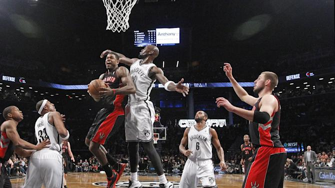 Brooklyn Nets forward Kevin Garnett (2) defends Toronto Raptors forward Amir Johnson (15) as teammates watch from the floor in the first half of an NBA basketball game, Monday, Jan. 27, 2014, in New York. (AP Photo/Kathy Willens)