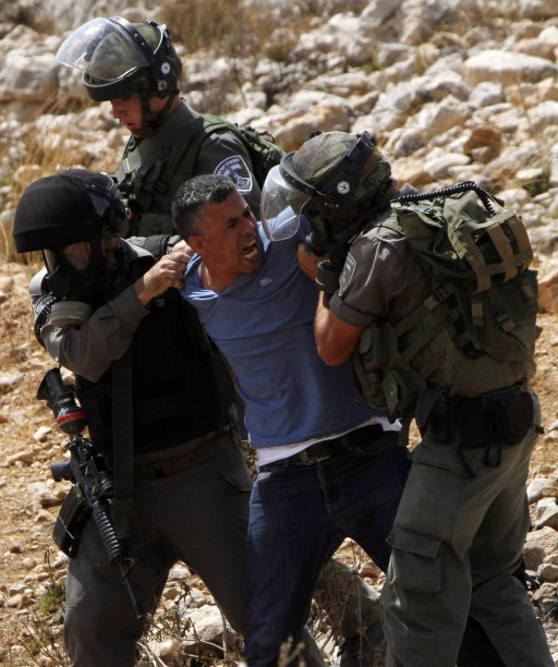 Israeli border policemen detain a Palestinian activist during clashes at a protest against a nearby Jewish settlement