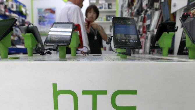 Customers look at HTC smartphones in a mobile phone shop in Taipei