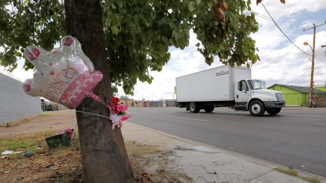 A makeshift memorial on a tree is shown, Thursday, Aug. 29, 2013, in Phoenix. An 8-year-old boy was driving his mother's car on a nighttime joyride with his 6-year-old sister when it crashed into a telephone pole, behind the tree, fatally injuring the girl, police said Thursday. (AP Photo/Matt York)