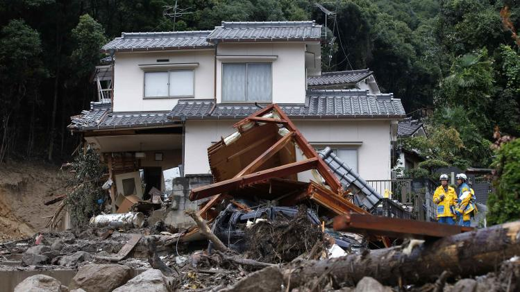 Police officers stand next to a damaged house at a site where a landslide swept through a residential area at Asaminami ward in Hiroshima