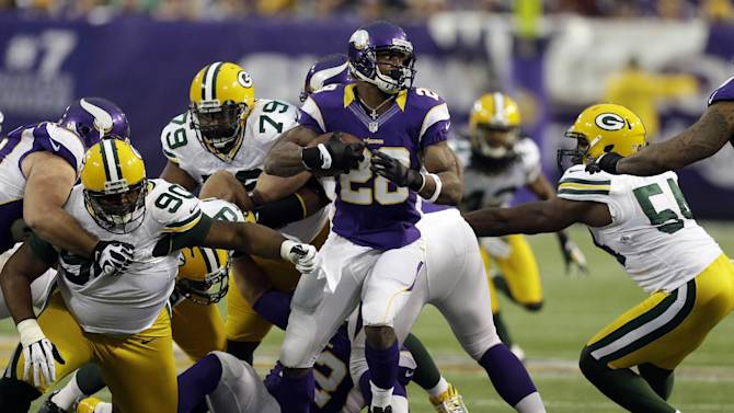 Minnesota Vikings running back Adrian Peterson, center, runs from Green Bay Packers defenders B.J. Raji (90), Ryan Pickett and Dezman Moses, right, during the first half of an NFL football game Sunday, Dec. 30, 2012, in Minneapolis. (AP Photo/Charlie Neibergall)