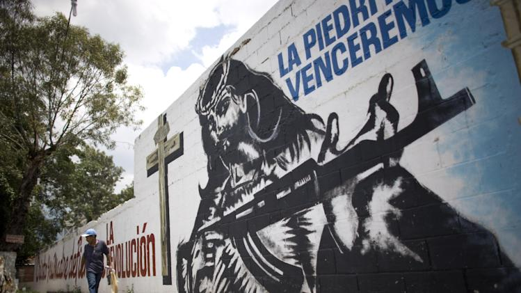 "FILE - In this Sept. 16, 2010 file photo, a man walks past a mural of Jesus Christ holding a machine gun alongside the words in Spanish ""La Piedrita Will Overcome"" in the La Piedrita area of the 23 of January neighborhood in Caracas, Venezuela.  On alert, and some apparently on edge, are hundreds of well-armed toughs spread through the hills of metropolitan Caracas who have been blamed for strong-armed intimidation of political opponents of Venezuela's late President Hugo Chavez and worse. As Venezuela ponders the next steps after Chavez's death Tuesday, the late leader's most uncompromising, and radical supporters make up a menacing unknown in a country brimming with guns and afflicted by the world's second-highest murder rate. (AP Photo/Ariana Cubillos, File)"