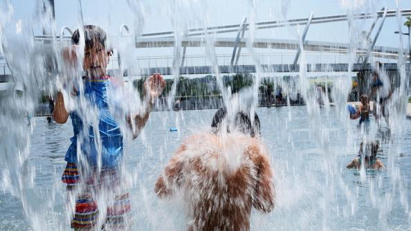 Ten-year-old Lilly Hwang-Geddes (L) of Ithaca, New York, plays in a fountain at the Yards Park July 5, 2012 in Washington, DC. A record heat wave has been in the area for more than a week. Weather forecast predicted the hot weather will last through Sunday with possible daily triple-digit temperature. (Photo by Alex Wong/Getty Images)