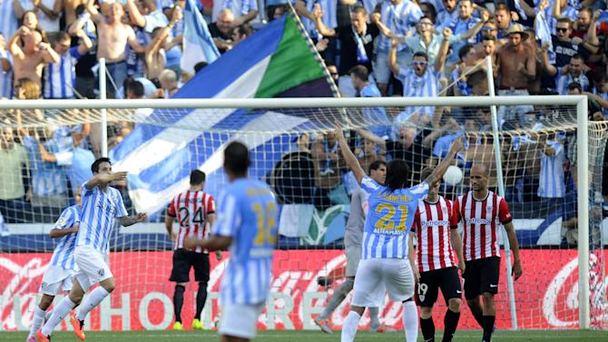 Malaga's midfielder Luis Alberto Romero (L) celebrates after scoring the opener on a penalty kick during the Spanish league football match Malaga CF vs Athletic Club Bilbao at the La Rosaleda stadium in Malaga on August 23, 2014