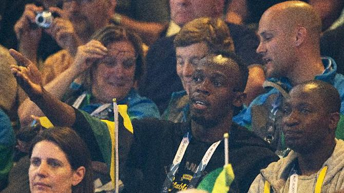 "Double Olympic champion Usain Bolt of Jamaica, centre, watches the women's pool A netball match between Jamaica and New Zealand at the Commonwealth Games Glasgow 2014, in Glasgow, Scotland, Wednesday, July, 30, 2014. Bolt is the center of attention at the Commonwealth Games after mingling with British royalty on Tuesday and being quoted in a British National newspaper saying that he was ""not really"" having fun in Glasgow although Bolt scrambled Wednesday to deny he made a derogatory comment about the ""Friendly Games."" (AP Photo/Alastair Grant)"