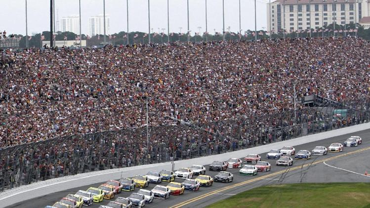 Danica Patrick, front left,and Jeff Gordon, front right, leads the pack to start the NASCAR Daytona 500 Sprint Cup Series auto race at Daytona International Speedway, Sunday, Feb. 24, 2013, in Daytona Beach, Fla. (AP Photo/David Graham)