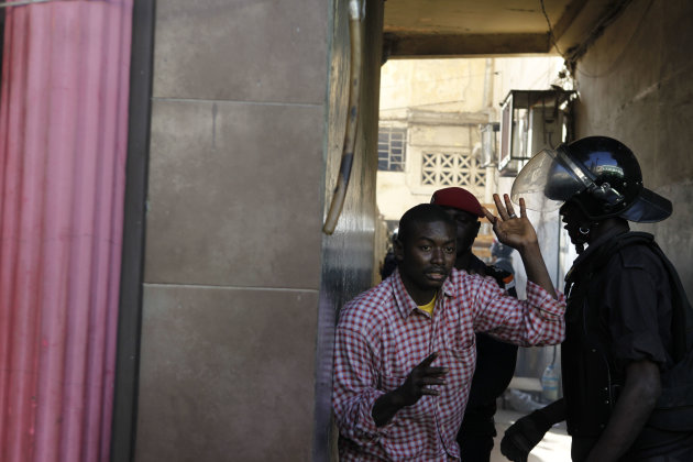 An anti-government protester is arrested by police after trying to hide in a courtyard, on a central boulevard in Dakar, Senegal Sunday, Feb. 19, 2012. Protesters demanding the departure of Senegal's