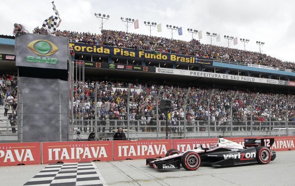 IndyCar driver Will Power, of Australia, gets the checkered flag as he wins the IndyCar Sao Paulo 300 in Sao Paulo, Brazil, Sunday, April 29, 2012. (AP Photo/Andre Penner)