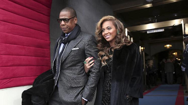 Recording artists Jay-Z and Beyonce arrive on the West Front of the Capitol in Washington, Monday, Jan. 21, 2013, for the Presidential Barack Obama's ceremonial swearing-in ceremony during the 57th Presidential Inauguration.  (AP Photo/Win McNamee, Pool)