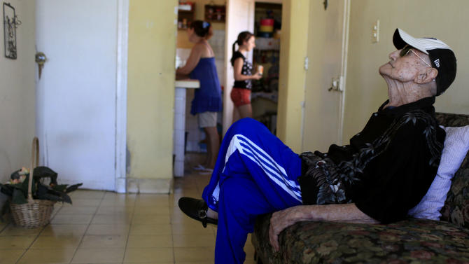 In this April 23, 2013 photo, Conrado Marrero, the world's oldest living former major league baseball player, sits in his home two days before is 102nd birthday, in Havana, Cuba.  In addition to his longevity, the former Washington Senator has much to celebrate this year. After a long wait, he finally received a $20,000 payout from Major League baseball granted to old-timers who played between 1947 and 1979. The money had been held up since 2011 due to issues surrounding the 51-year-old U.S. embargo on Cuba, which prohibits most bank transfers to the Communist-run island. But the payout finally arrived in two parts, one at the end of last year, and the second a few months ago, according to Marrero's family. (AP Photo/Franklin Reyes)