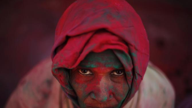 A widow daubed in colours takes part in Holi celebrations at Vrindavan