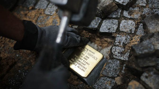 """German artist Gunter Demnig sets a so called 'Stolperstein', or stumbling stone, to remember Nazi victim Mildred Fish-Harnack and her husband Arvid Harnack in Berlin, Friday, Sept. 20, 2013. The American teacher who resisted Adolf Hitler and was executed by the Nazis has been honored in a ceremony attended by U.S. diplomats and German officials. At an event Friday in Berlin an artist placed small commemorative paving stones in front of the last home of Mildred Fish-Harnack, who grew up in Milwaukee, and her German husband Arvid Harnack. The couple was part of a German group known as the """"Red Orchestra"""" that tried to encourage resistance against the Nazis and fed information to the Soviets. Plaque reads : Here lived Mildred Harnack, born as Fish, 1902, arrested Sept. 7, 1942, High Treason, Berlin Ploetzensee ( name of the prison), Murdered Feb. 16, 1943. (AP Photo/Markus Schreiber)"""