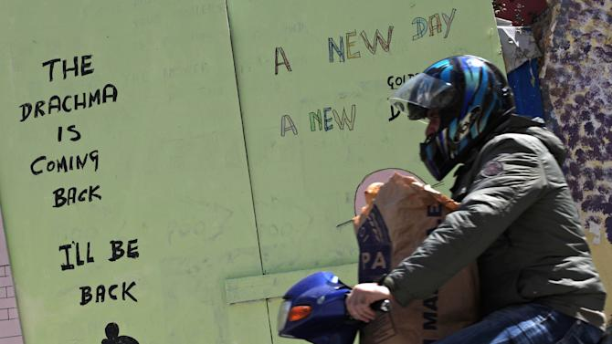 A motorist drives next a graffiti, in central Athens, on Tuesday, May 22, 2012. Greece gets underway for crucial June 17 elections with the vote seen as a choice on whether debt-stricken Greece stays in the euro.(AP Photo/Petros Giannakouris)