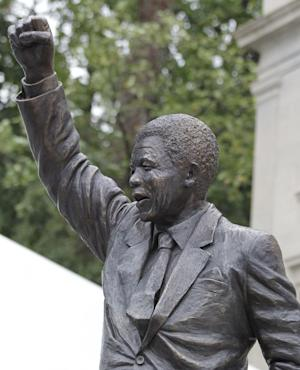 A statue of former South African President Nelson Mandela stands outside the newly-renovated South African embassy in Washington after its unveiling on Saturday, Sept. 21, 2013. The 9-foot statue was made by Cape Town sculptor Jean Doyle. (AP Photo/Luis M. Alvarez)