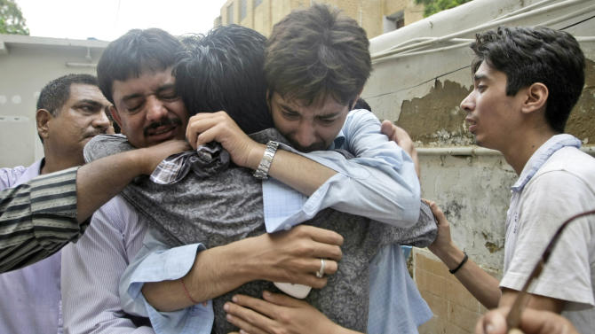 In this Wednesday, Sept. 12, 2012, photo, Pakistanis comfort each others after learning the death of a relative, who was killed in a fire at a garment factory, in Karachi, Pakistan. At the only morgue in Pakistan's largest city lie the blackened remains of 32 people killed in one of the worst industrial accidents in the country's history, wrapped in white plastic body bags waiting for DNA tests to determine who they are and where they belong. (AP Photo/Fareed Khan)