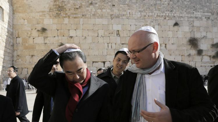 Chinese Foreign Minister Wang touches his Jewish skull cap as the Western Wall is seen in the background, during his visit to Jerusalem's Old City
