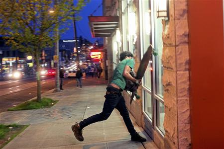 A demonstrator attempts to break a window of a pharmacy on Capitol Hill during May Day demonstrations in Seattle, Washington May 1, 2013. REUTERS/Matt Mills McKnight