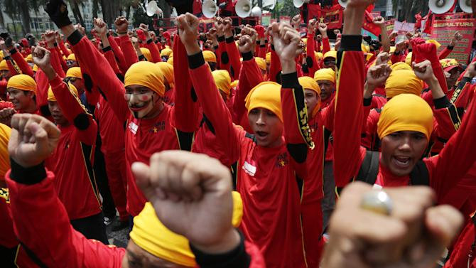 Indonesian workers shout slogans during a rally against cheap wages in Jakarta, Indonesia, Monday, Sept 15, 2014. Thousands of factory workers took to the streets in the capital to protest against outsourcing and low wages.  (AP Photo/Achmad Ibrahim)