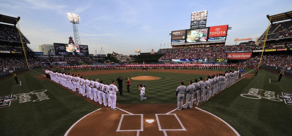 Teams line up during the national anthem at Angel Stadium prior to the Los Angeles Angels' baseball game against the Kansas City Royals, Friday, April 6, 2012, in Anaheim, Calif. (AP Photo/Mark J. Terrill)