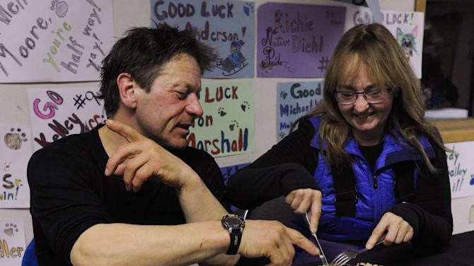 Four-time Iditarod champion Martin Buser and his wife, Kathy Chapoton, eat a special meal prepared for the First to the Yukon award winner in Anvik, Alaska, during the Iditarod Trail Sled Dog Race, early Friday, March 8, 2013. Besides the meal, there are two more gifts for the first musher: $3,500, served on a gold pan, but all in single $1 bills, and a bottle of champagne. (AP Photo/Anchorage Daily News, Bill Roth)