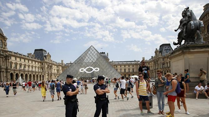 FILE - In this Aug. 2, 2013 file photo French police officers stand guard at the Louvre Museum, Paris, during a visit of French Interior Minister Manuel Valls, unseen, during a tour focusing on security at the city's top tourist areas. Police have arrested a group of pickpockets who dressed like tourists in order to target visitors of Paris' most famous museums and monuments. They operated at the Louvre, the Musee d'Orsay, the Eiffel Tower and the Chateau de Versailles, bringing in as much as 2,000 euros ($2,700) per day by grabbing the wallets of tourists. (AP Photo/Francois Mori, File)