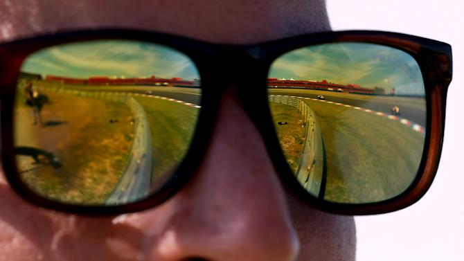 MotoGP motorcycles are reflected in a track official's sunglasses during a free practice session at Argentina's MotoGP Grand Prix in Termas de Rio Hondo
