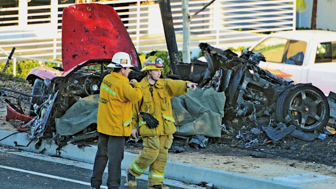 "FILE - In this Nov. 30, 2013, file photo, sheriff's deputies work near the wreckage of a Porsche that crashed into a light pole on Hercules Street near Kelly Johnson Parkway in Valencia, Calif. A coroner's report says the Porsche carrying ""Fast & Furious"" star Paul Walker may have been going 100 mph or more before it crashed, killing both Walker and the driver. The report released Friday, Jan. 3, 2014, by the Los Angeles County coroner's office says that Roger Rodas, Walker's friend and financial adviser, was driving the 2005 Porsche Carrera GT at an unsafe speed, estimated by witnesses to be 100 mph or more. (AP Photo/The Santa Clarita Valley Signal, Dan Watson, File)"