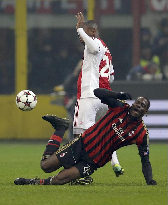 AC Milan forward Mario Balotelli, is tackled by Ajax's Thulani Serero during a Champions League, Group H, soccer match at the San Siro stadium, in Milan, Italy, Wednesday, Dec.11, 2013