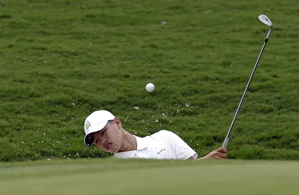 Amateur Guan Tianlang, 14, of China, hits out of a bunker onto the 17th green during the second round of the Byron Nelson Championship golf tournament Friday, May 17, 2013, in Irving, Texas. (AP Photo/Tony Gutierrez)