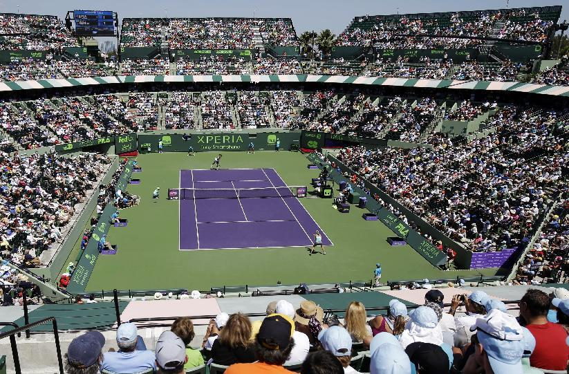 Fans watch as Serena Williams, rear, serves to Maria Sharapova, of Russia, during the final match of the Sony Open tennis tournament, Saturday, March 30, 2013, in Key Biscayne, Fla. (AP Photo/Wilfredo Lee)
