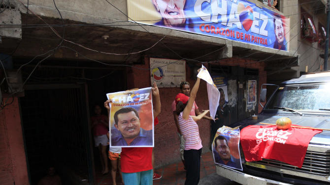 In this Sept. 16, 2012 photo, supporters of Venezuela's President Hugo Chavez wave campaign posters of him as opposition presidential candidate Henrique Capriles campaigns in the Petare shantytown of Caracas, Venezuela. From single mothers to construction workers, a segment of Chavez supporters have been turning away from the president and instead considering new leadership. They've become key to the Oct. 7 presidential vote and Capriles' strategy. (AP Photo/Fernando Llano)