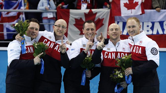 Canada's curlers, from left, Caleb Flaxey, Ryan Harnden, E.J. Harnden, Ryan Fry, and Brad Jacobs pose during flower ceremony after winning the men's curling gold medal at the 2014 Winter Olympics, Friday, Feb. 21, 2014, in Sochi, Russia. (AP Photo/Robert F. Bukaty)