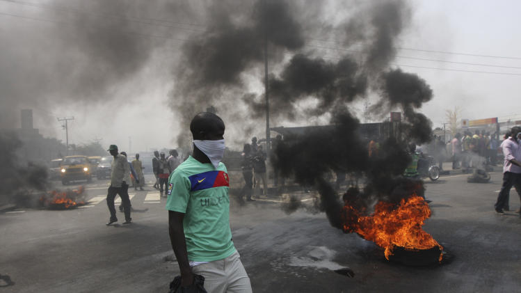 "FILE- An Unidentified man stands near burning tyres during a protest on a major road junction in the commercial capital of Lagos, Nigeria, during a fuel subsidy protest in this file photo dated Tuesday, Jan. 3, 2012, as angry mobs call on the government to keep a cherished consumer subsidy that had kept gas affordable for more than two decades. A 30-minute film documentary called ""Fuelling Poverty"" has been online for months, but it is revealed Sunday April 21, 2013, that Nigerian officials have refused its director Ishaya Bako permission to show it publicly in this oil-rich nation, as it focuses on the January 2012 protests and the alleged billions of dollars thought to have been swallowed up by greedy companies and the nation's elite. (AP Photo/Sunday Alamba, File)"