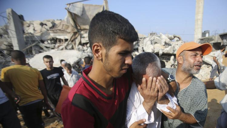 Palestinian man reacts as people search for victims under the rubble of a house in Rafah in the southern Gaza Strip