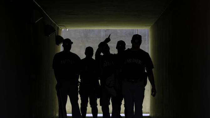 Seattle Mariners players enter the field through a tunnel before a spring training exhibition baseball game against the Los Angeles Dodgers Friday, March 6, 2015, in Phoenix. (AP Photo/John Locher)