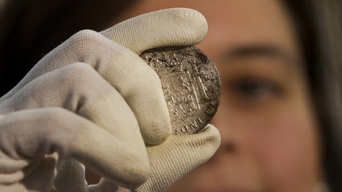 A worker of the ministry holds up for photographers a silver coin from the shipwreck of a 1804 galleon, on its first display to the media at a ministry building, in Madrid, Friday, Nov. 30, 2012. Spanish cultural officials have allowed the first peep at 16 tons (14.5 metric tons) of the shipwreck, 'Nuestra Senora de las Mercedes' a treasure worth an estimated $500 million that a U.S. salvage company gave up after a five-year international ownership dispute. (AP Photo/Daniel Ochoa de Olza)