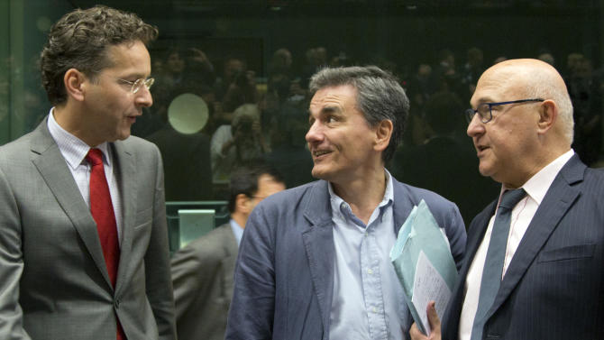 Greek Finance Minister Euclid Tsakalotos, center, speaks with Dutch Finance Minister Jeroen Dijsselbloem, left, and French Finance Minister Michel Sapin during a round table meeting of eurozone finance ministers at the EU LEX building in Brussels on Tuesday, July 7, 2015. Greek Prime Minister Alexis Tsipras was heading Tuesday to Brussels for an emergency meeting of eurozone leaders, where he will try to use a resounding referendum victory to eke out concessions from European creditors over a bailout for the crisis-ridden country. (AP Photo/Virginia Mayo)