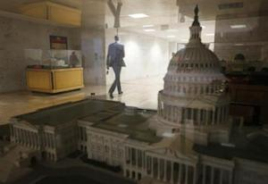 A staffer in the Dirksen Senate building walks past a scale model of the U.S. Capitol in Washington October 7, 2013. REUTERS/Jason Reed