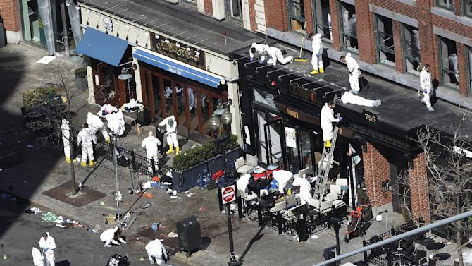 In this  Wednesday, April 17, 2013 file photo, investigators comb through the scene of one of the blast sites of the Boston Marathon explosions in Boston.  Three more suspects were taken into custody in the Boston Marathon bombing case, including two college friends of Dzhokhar Tsarnaev who came to the U.S. from Kazakhstan, officials said Wednesday May 1, 2013. (AP Photo/Julio Cortez)