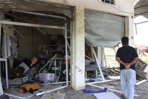 A man looks at a shop, site of a car bomb attack in Hilla